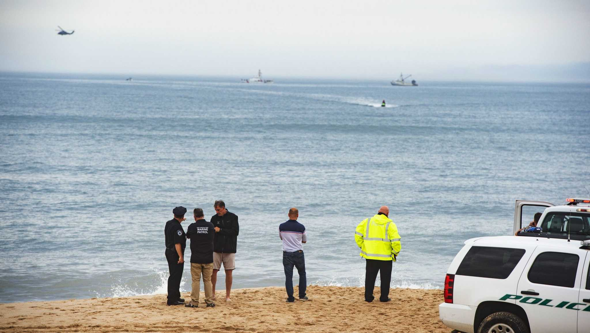 Members of the New York State park police look near the scene of a plane crash in the ocean off Indian Wells Beach in Amagansett, N.Y., Saturday, June 2, 2018.