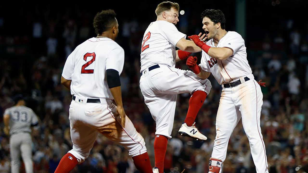 Boston Red Sox's Andrew Benintendi, right, celebrates his game-winning RBI single with Brock Holt, center, and Xander Bogaerts (2) during the tenth inning of a baseball game against the New York Yankees in Boston, Monday, Aug. 6, 2018