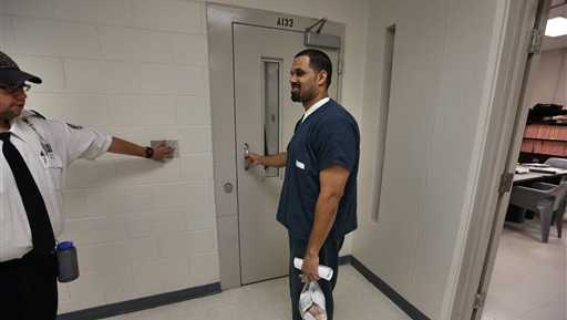 In this May 7, 2014 photo, Rene Lima-Marin talks with a guard who escorts him back to the prison block following an interview with The Associated Press about the circumstances of his sentencing and incarceration, inside Kit Carson Correctional Center, a privately operated prison in Burlington, Colo. Lima-Marin, who was sent back to prison after being mistakenly released 90 years early, says it was cruel and unusual punishment to put him back behind bars after he reformed his life. An appeal filed Wednesday, Aug. 20, 2014 in his case also says his constitutional rights were violated when a judge in January ordered him to finish his sentence after he started a family during nearly six years of freedom. A judge in 2000 sentenced Lima-Marin to a total of 98 years in prison for multiple counts stemming from the robbery of two video stores when Lima-Marin was 20.