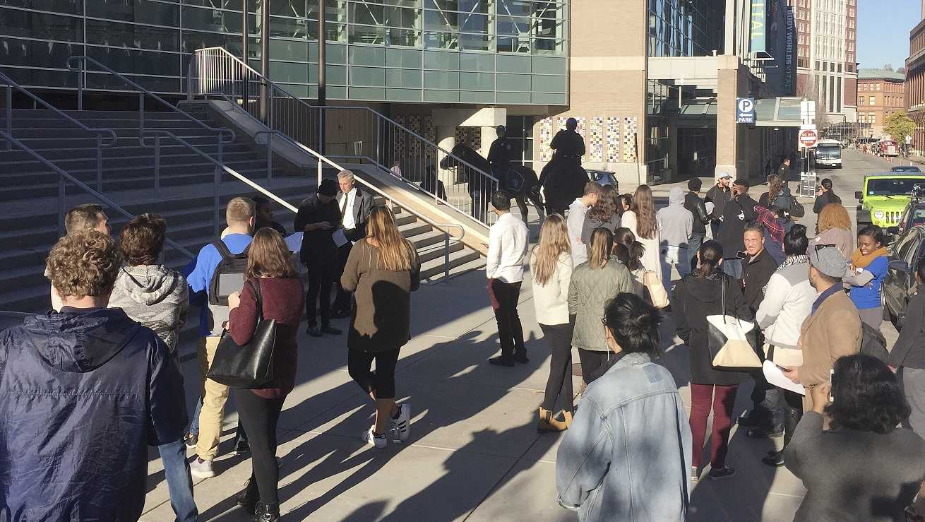 Voters stand outside the Dunkin Donuts Center, being used as a polling place in Providence, R.I., after it was briefly evacuated.