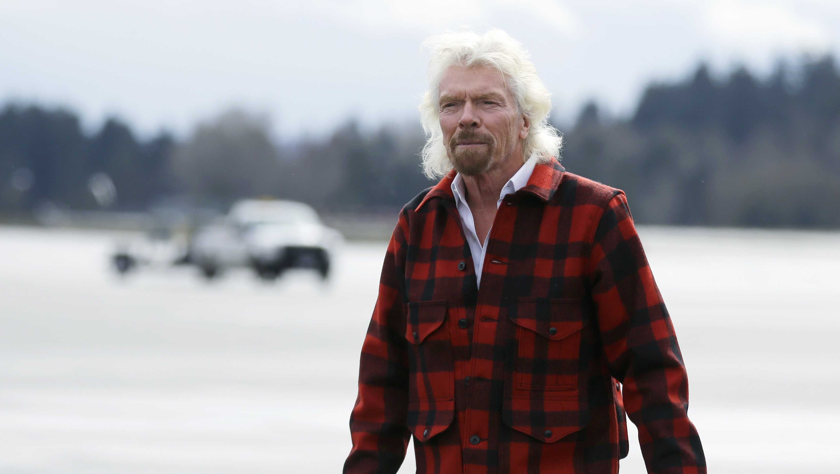 Sir Richard Branson, founder of Virgin Atlantic and the Virgin Group, walks on the tarmac after he arrived on a flight from London to Seattle, Monday, March 27, 2017, at Seattle-Tacoma International Airport in Seattle.