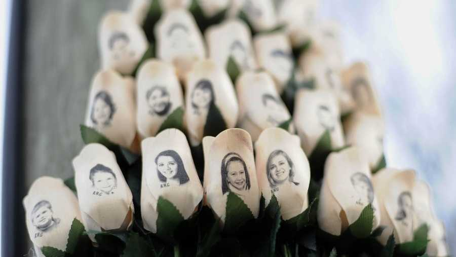 In this Jan. 14, 2013, file photo, white roses with the faces of victims of the Sandy Hook Elementary School shooting are attached to a telephone pole near the school in Newtown, Conn.