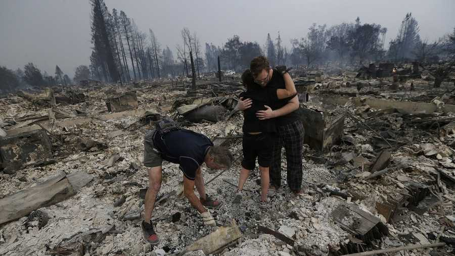 Michael Pond, left, looks through ashes as his wife Kristine, center, gets a hug from Zack Thurston, their daughter's boyfriend, while they search the remains of their home destroyed by fires in Santa Rosa.