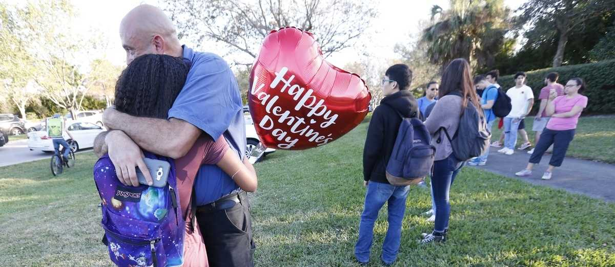 Family members embrace following a shooting at Marjory Stoneman Douglas High School.