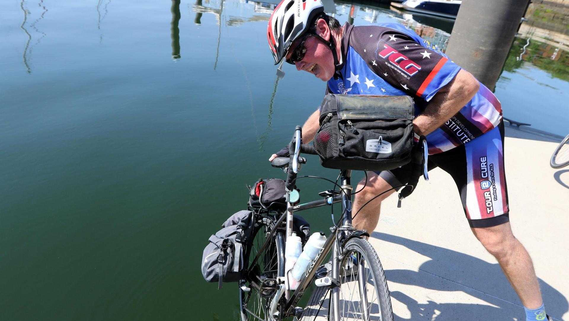 Wellesley girls basketball coach Glen Magpiong dips his bike wheel into the Atlantic Ocean in Charlestown before starting his cross-country bike trip on July 31.