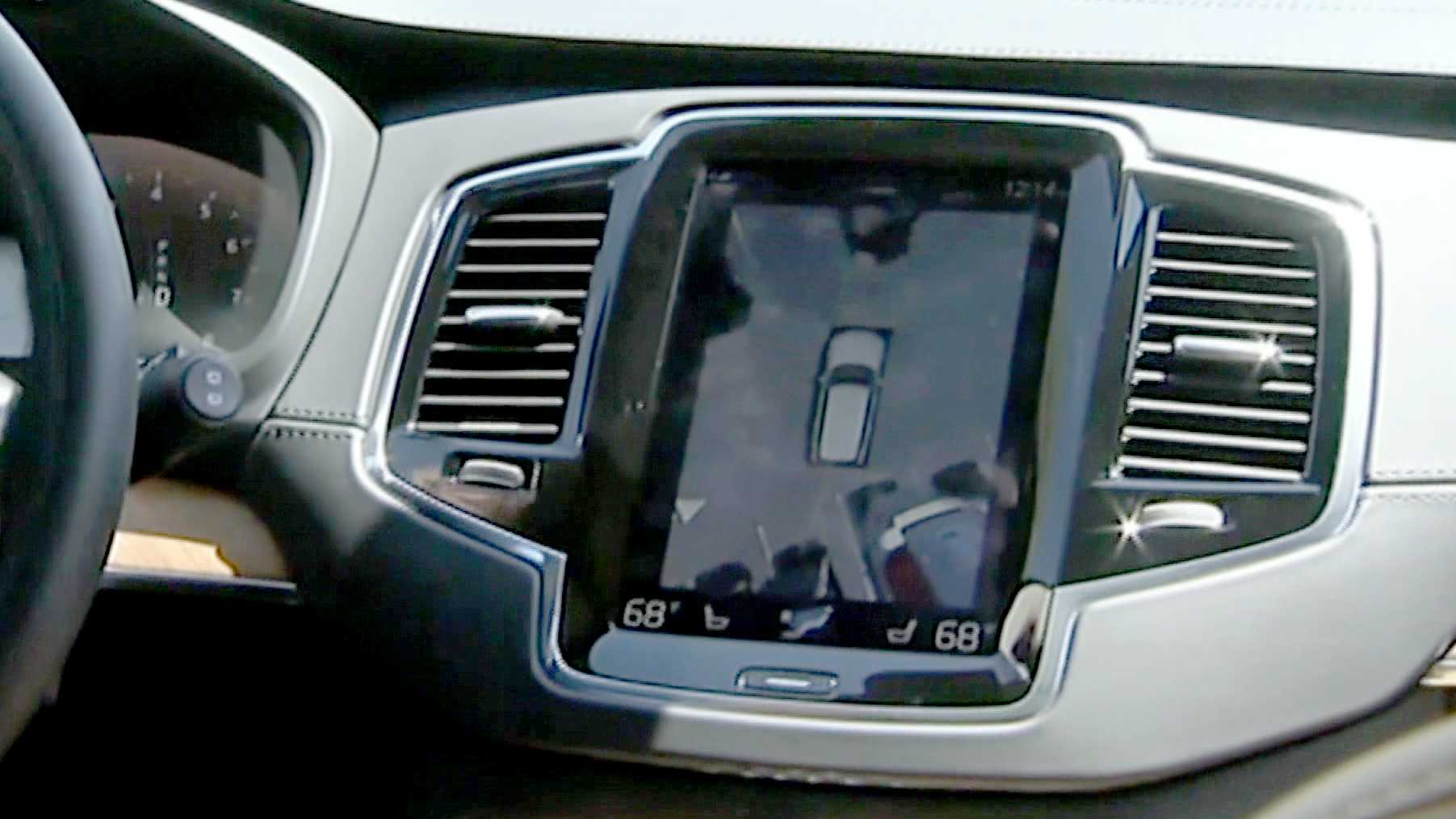 The display screen shows the progress of a self-driving SUV as it parks.
