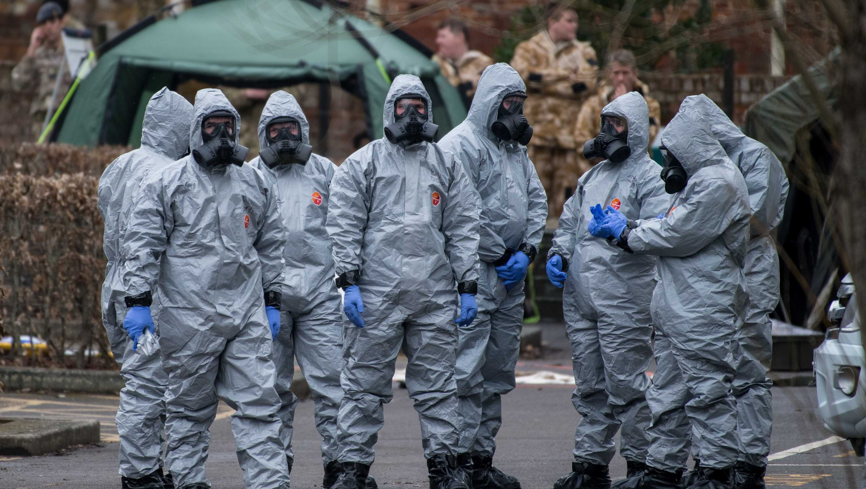 Military personnel wearing protective suits remove a police car and other vehicles from a public car park as they continue investigations into the poisoning of Sergei Skripal on March 11, 2018 in Salisbury, England.