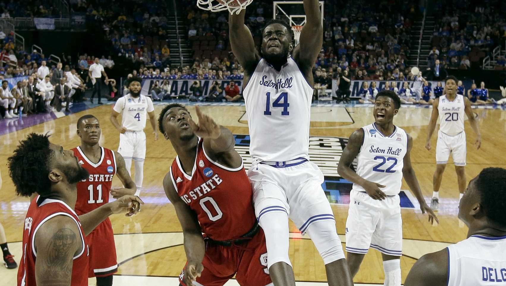 Seton Hall forward Ismael Sanogo (14) gets past North Carolina State forward Abdul-Malik Abu (0) to dunk the ball during the first half of an NCAA college basketball tournament first-round game Thursday, March 15, 2018, in Wichita, Kan.
