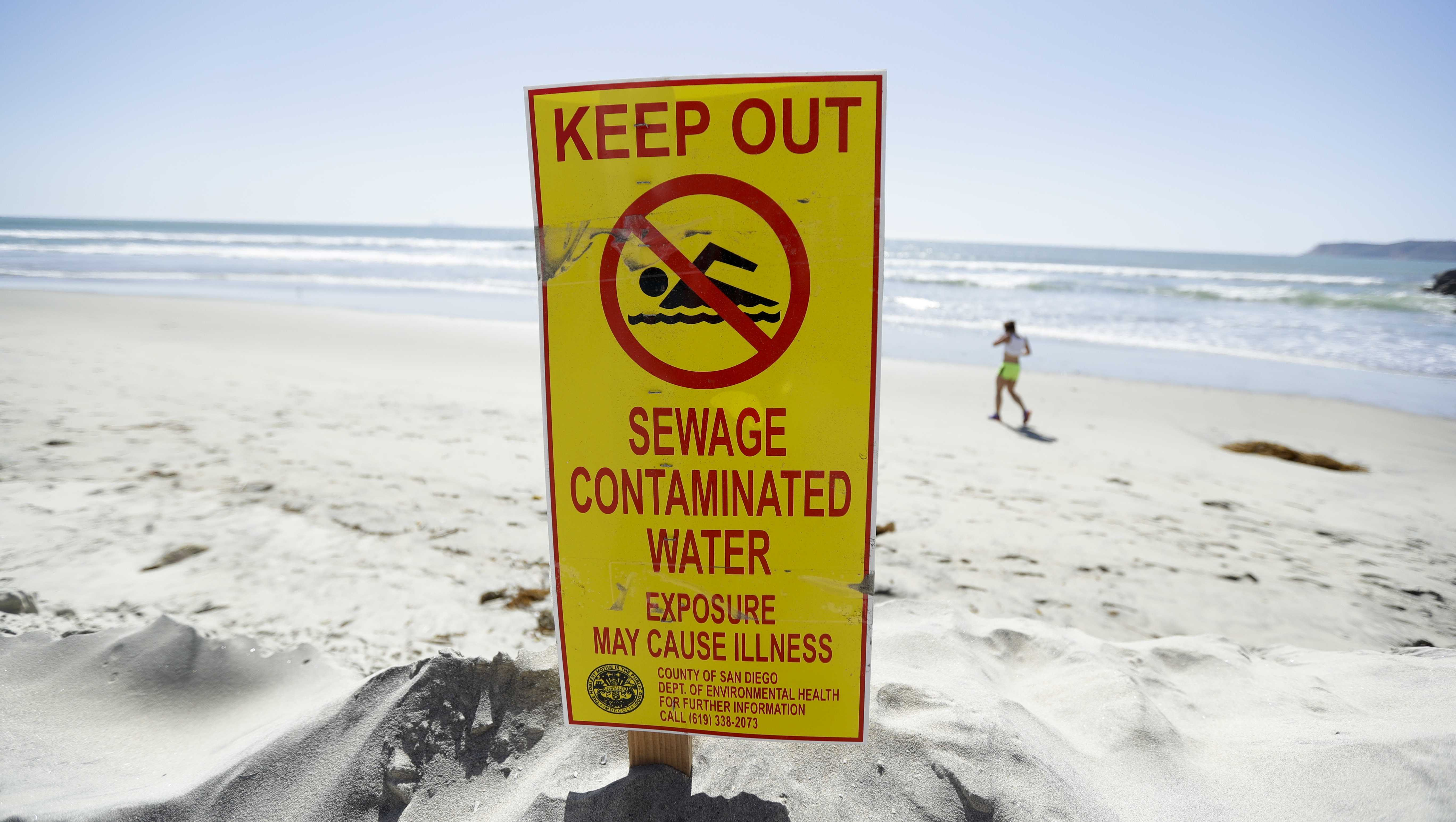 A sign warns of sewage contaminated ocean waters on a beach Wednesday, March 1, 2017, in Coronado, Calif. Coronado and Imperial Beach waters remain closed to swimmers and surfers Wednesday after more than 140 million gallons of raw sewage spilled into the Tijuana River in Mexico and flowed north of the border for weeks in February, according to a report.