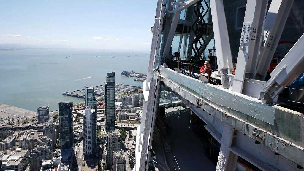 A construction crew works near the top of the 1,070-foot Salesforce Tower.