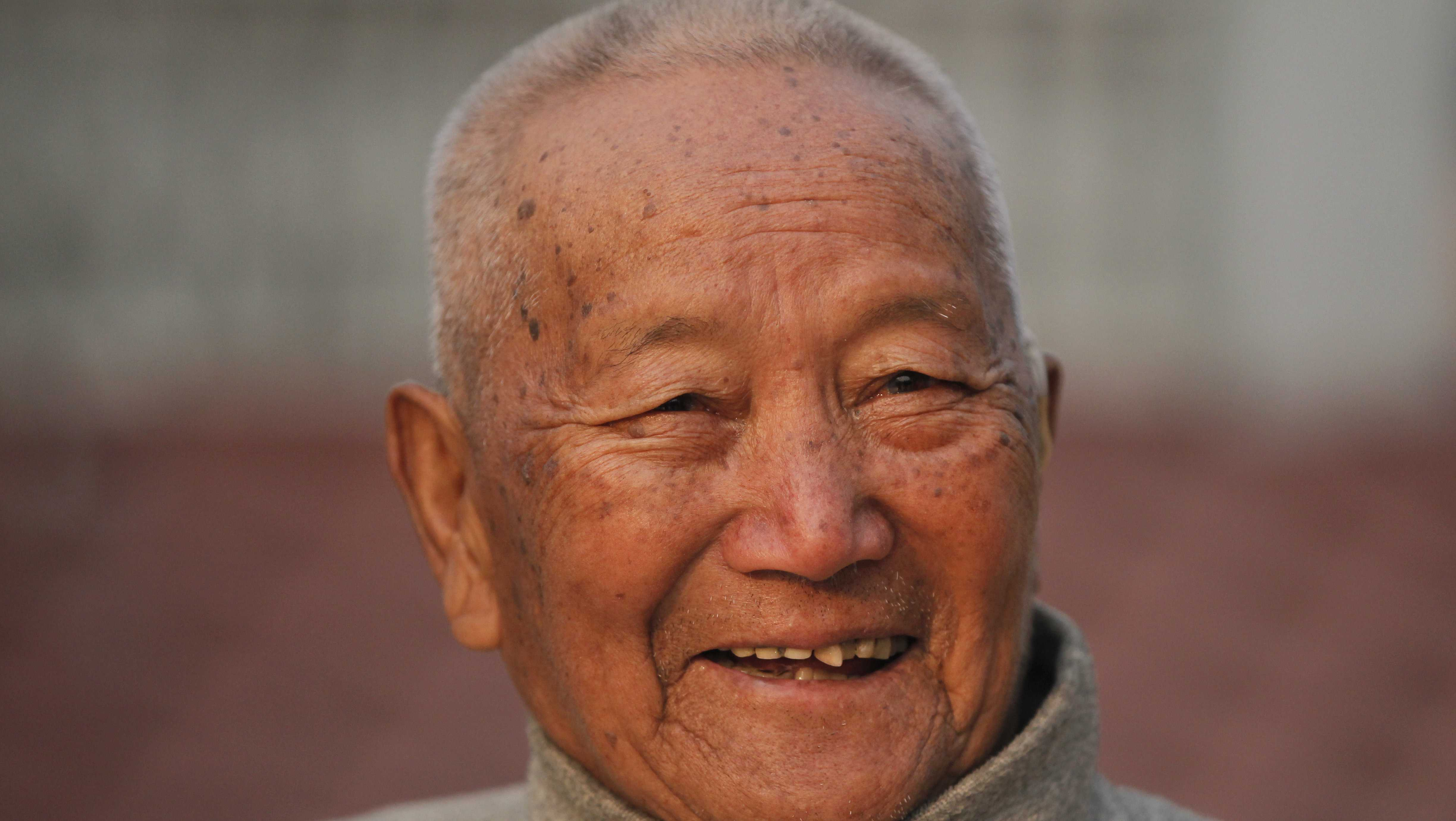 In this April 12, 2017 file photo, Nepalese mountain climber Min Bahadur Sherchan, 85, smiles as he finishes his morning yoga workout at his residence in Kathmandu, Nepal. Officials say Sherchan who was attempting to scale Mount Everest to regain his title as the oldest person to scale the world's highest peak has died at the base camp on Saturday, May 6, but was not clear about the cause of the death.