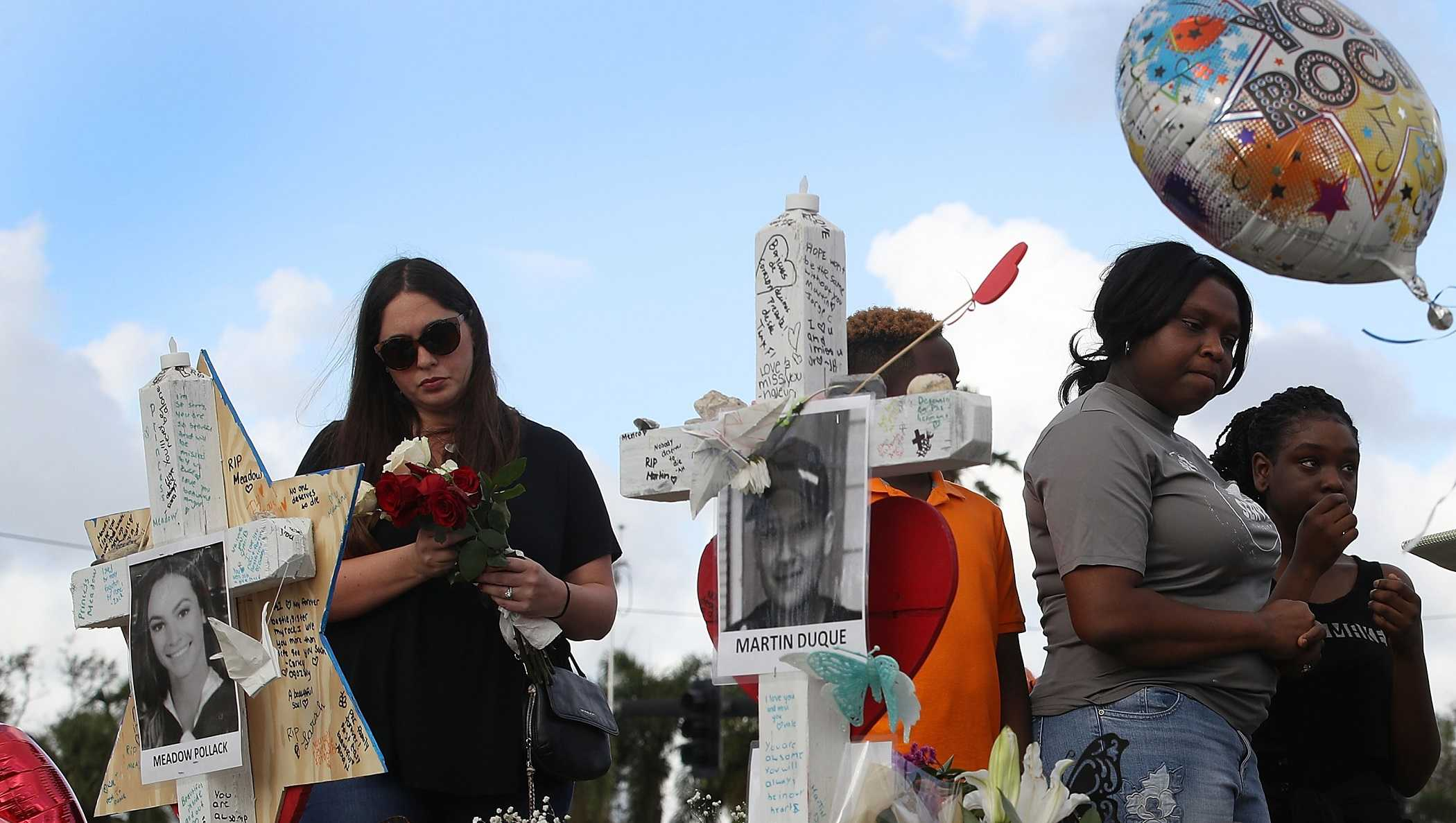 People visit a makeshift memorial setup in front of Marjory Stoneman Douglas High School on February 19, 2018 in Parkland, Florida. Police arrested and charged 19 year old former student Nikolas Cruz for the February 14 shooting that killed 17 people.