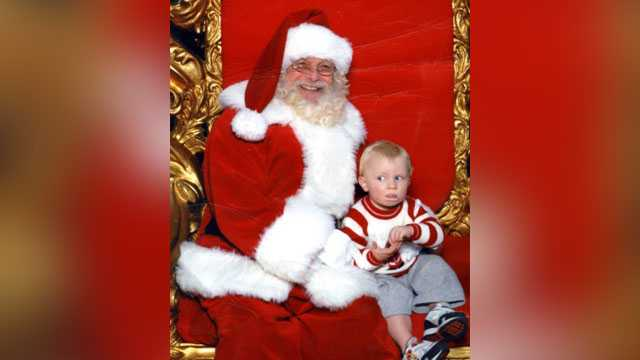 Little boy signs for help while sitting with Santa