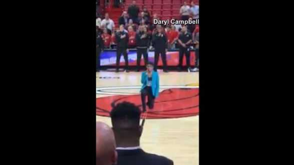 singer kneels during national anthem