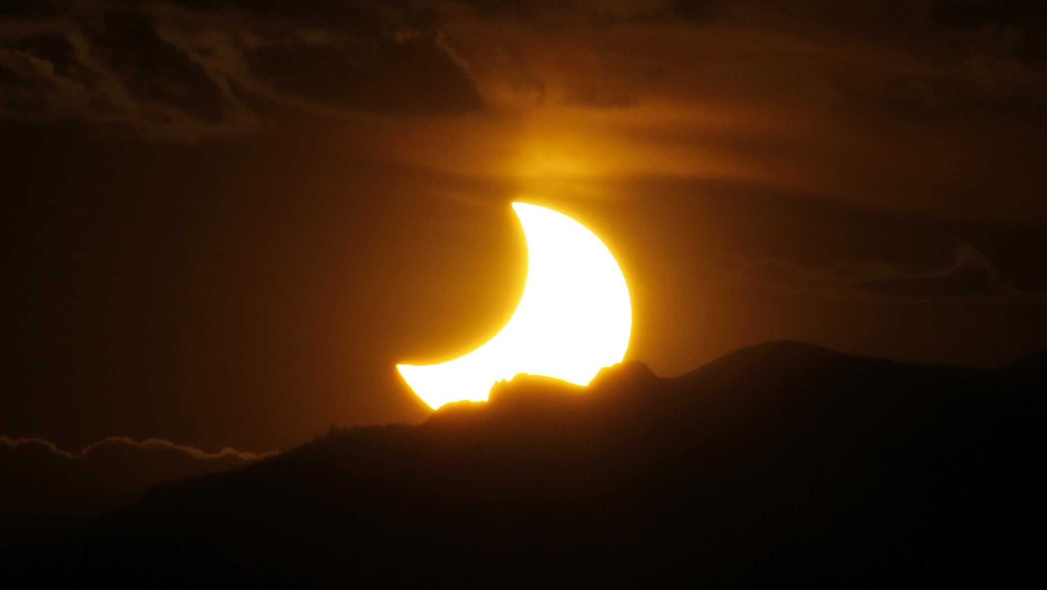 In this May 20, 2012, file photo, the annular solar eclipse is seen as the sun sets behind the Rocky Mountains from downtown Denver.
