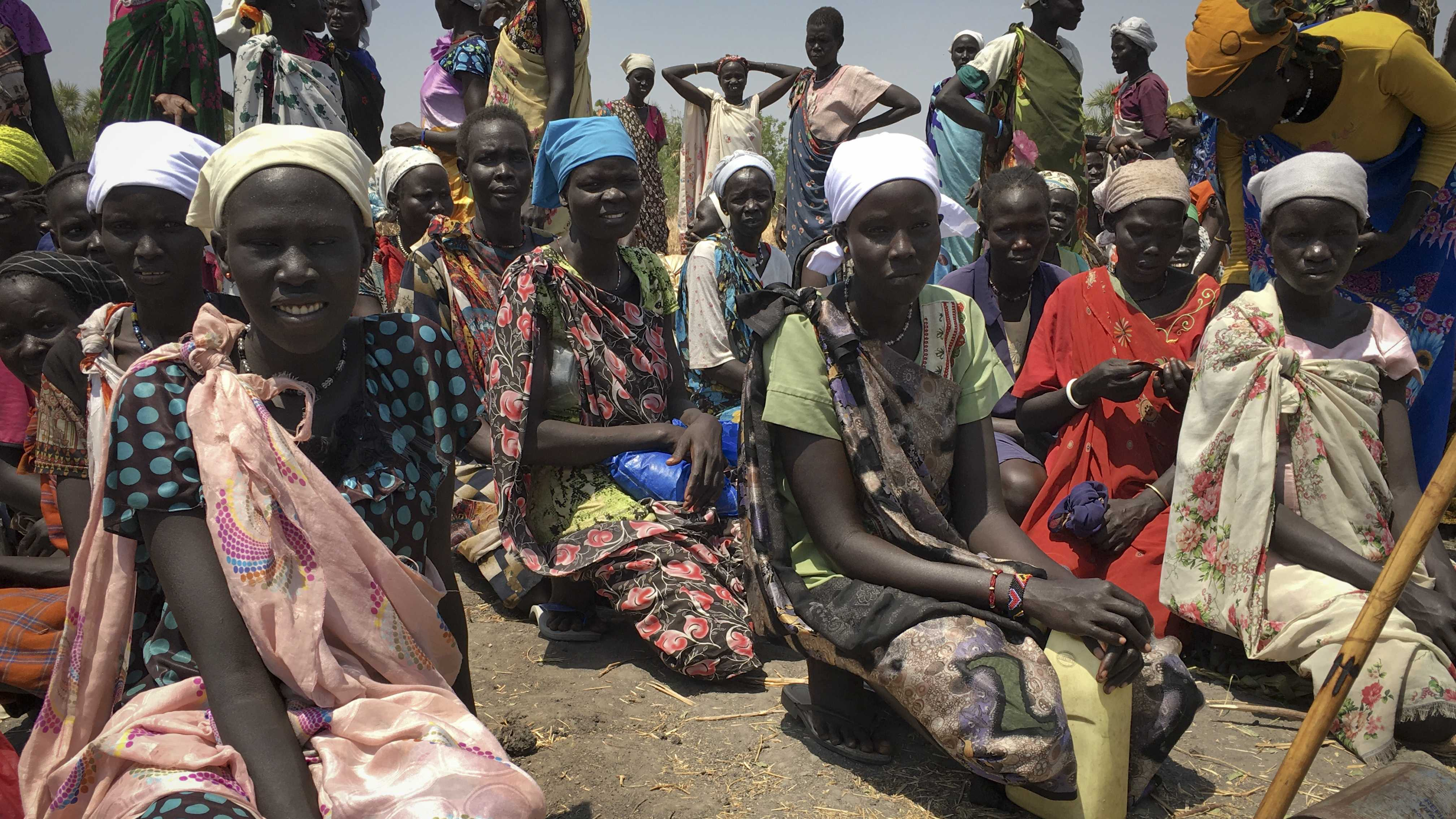 In this photo taken Wednesday, March 1, 2017, women sit in line on the ground waiting to receive food distributed by the World Food Program (WFP) in Padeah, South Sudan. South Sudanese who fled famine and fighting in Leer county emerged from South Sudan's swamps after months in hiding to receive food aid being distributed by the World Food Program.