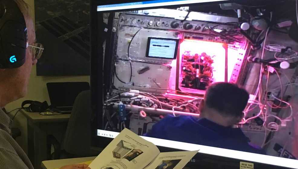 Charles Spern, a Veggie project engineer with the Engineering Services Contract, relays messages from the Kennedy Space Center Veggie team to assist the crew during harvest.
