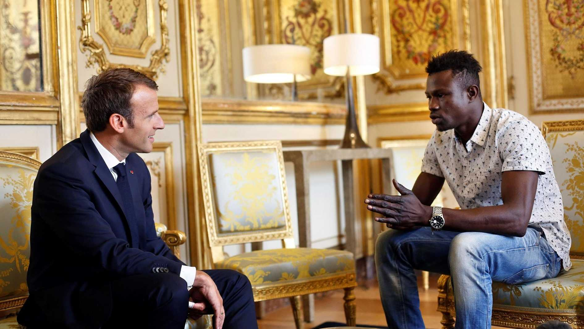 French President Emmanuel Macron (L) speaks with Mamoudou Gassama, 22, from Mali, at the presidential Elysee Palace in Paris, on May, 28, 2018.