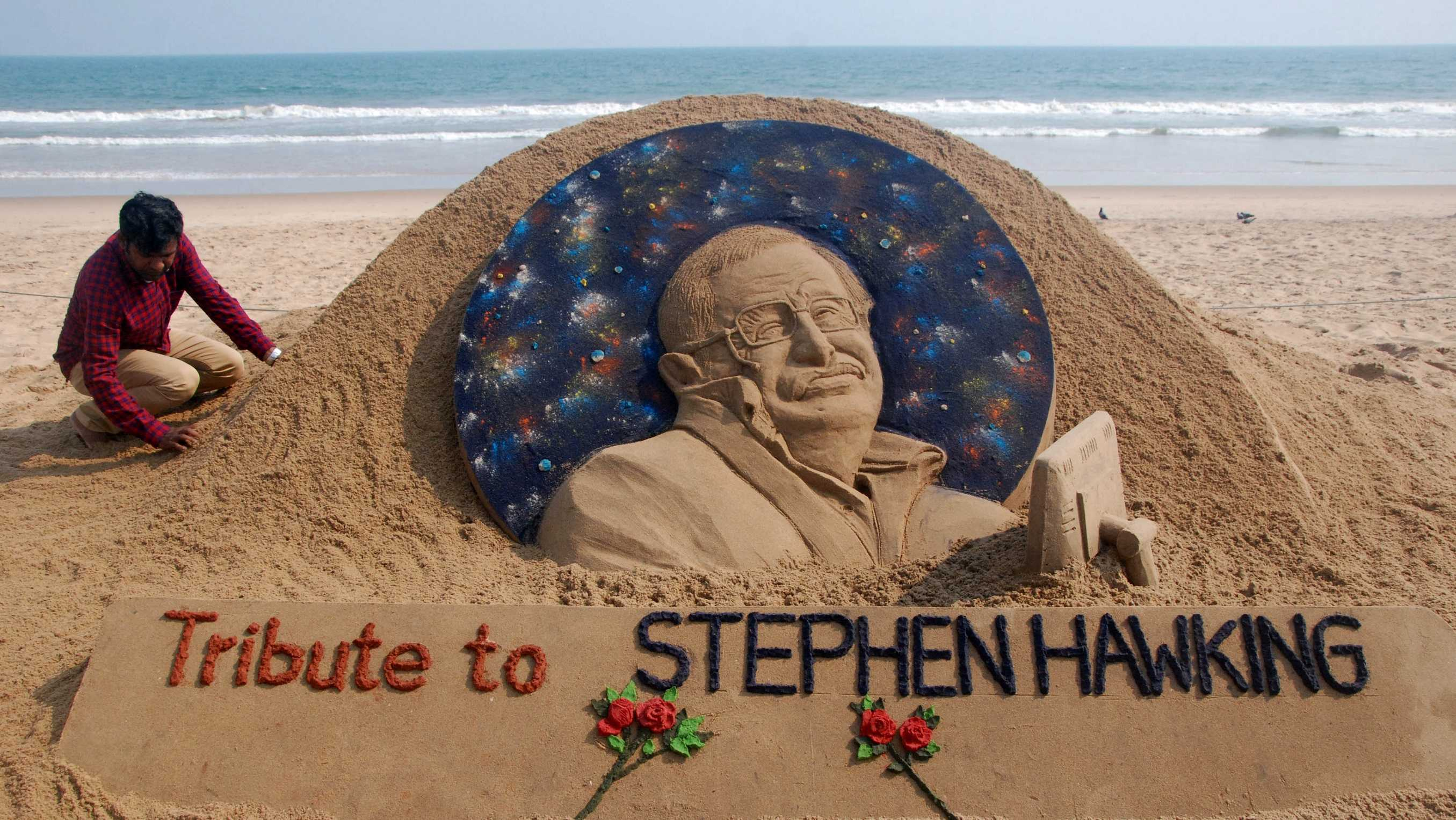 Sand artist Sudarsan Patnaik gives final touches to a sculpture in honor of British physicist and award-winning author Stephen Hawking at Puri Beach in Odisha, India, on March 14, 2018.