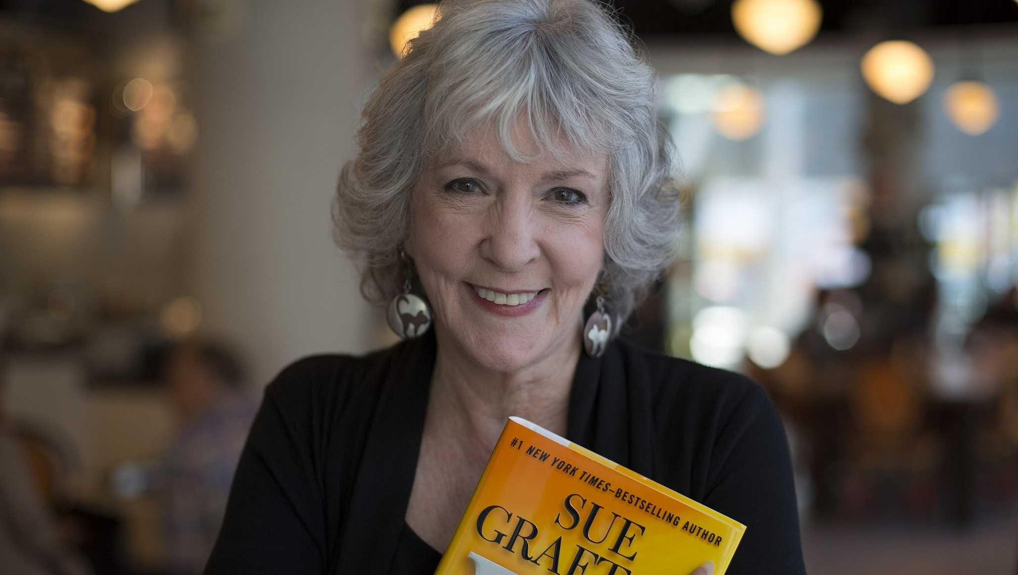 Detective novelist Sue Grafton poses with her 23rd book 'W' at a coffee shop in the Toronto Reference Library, October 3, 2013.