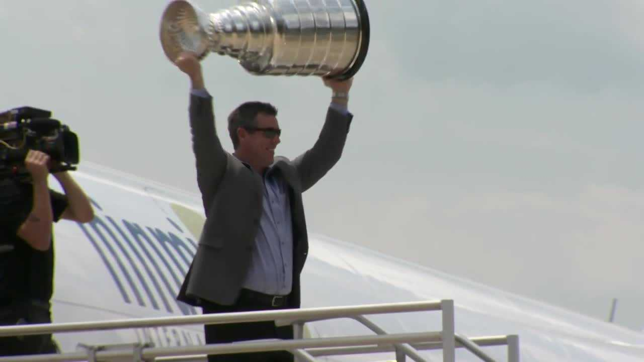 Penguins coach Mike Sullivan holds the Stanley Cup over his head.