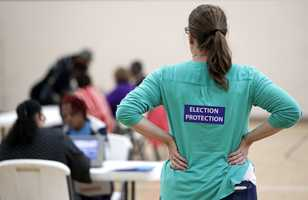 A poll watcher, right, watches as voters sign in at a Tennessee community building on Election Day.