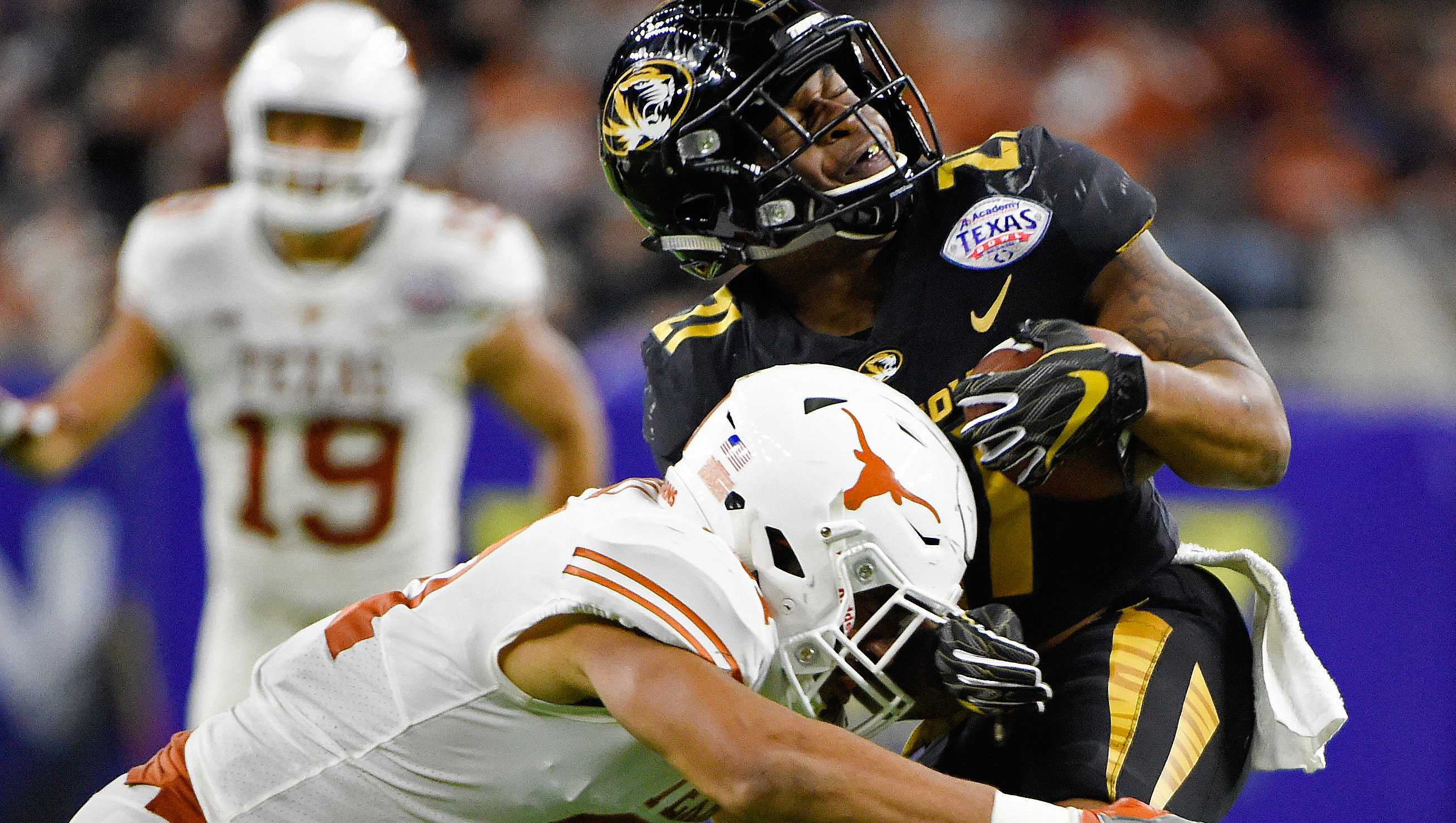 Missouri running back Ish Witter, right, is hit by Texas defensive back Jason Hall during the first half of the Texas Bowl NCAA college football game Wednesday, Dec. 27, 2017, in Houston. (AP Photo/Eric Christian Smith)