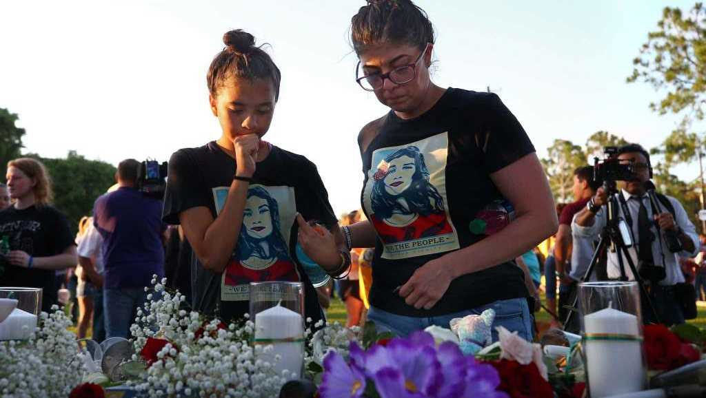 People dropped flowers in honor for the victims of the Santa Fe High School mass shooting during a vigil at Texas First Bank Friday, May 18, 2018, in Santa Fe, Texas.