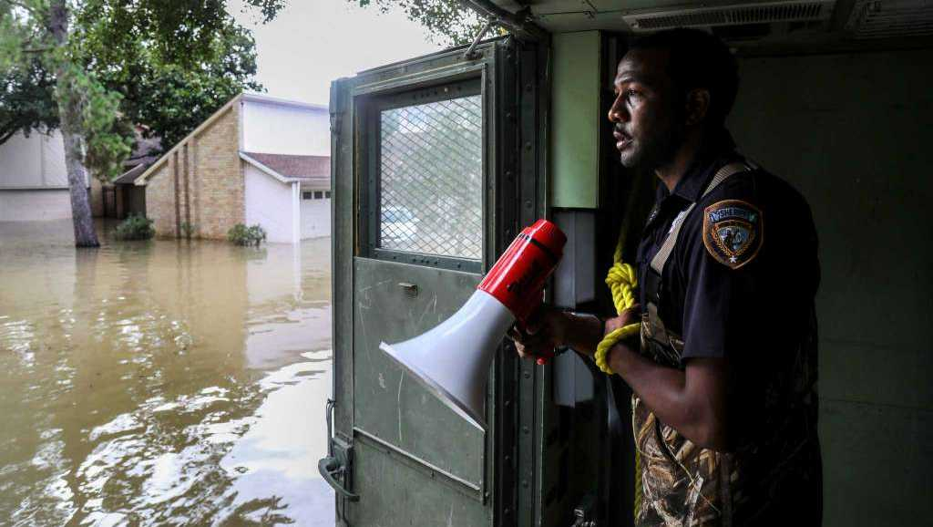Sheriff's Deputy Rick Johnson pauses to listen for people's voices Wednesday while searching for flood victims in a neighborhood inundated by water from the Addicks Reservoir in Houston.