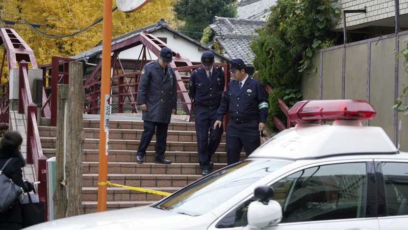Police officers walk near the scene of a stabbing incident at Tomioka Hachimangu shrine in Tokyo Friday, Dec. 8, 2017. Police say three people have died in the stabbing attack on Thursday night at the prominent shrine, including the head priest and the attacker, who apparently took his own life.