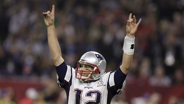 New England Patriots' Tom Brady raises his arms after scoring a touchdown during overtime of the NFL Super Bowl 51 football game against the Atlanta Falcons, Sunday, Feb. 5, 2017, in Houston.