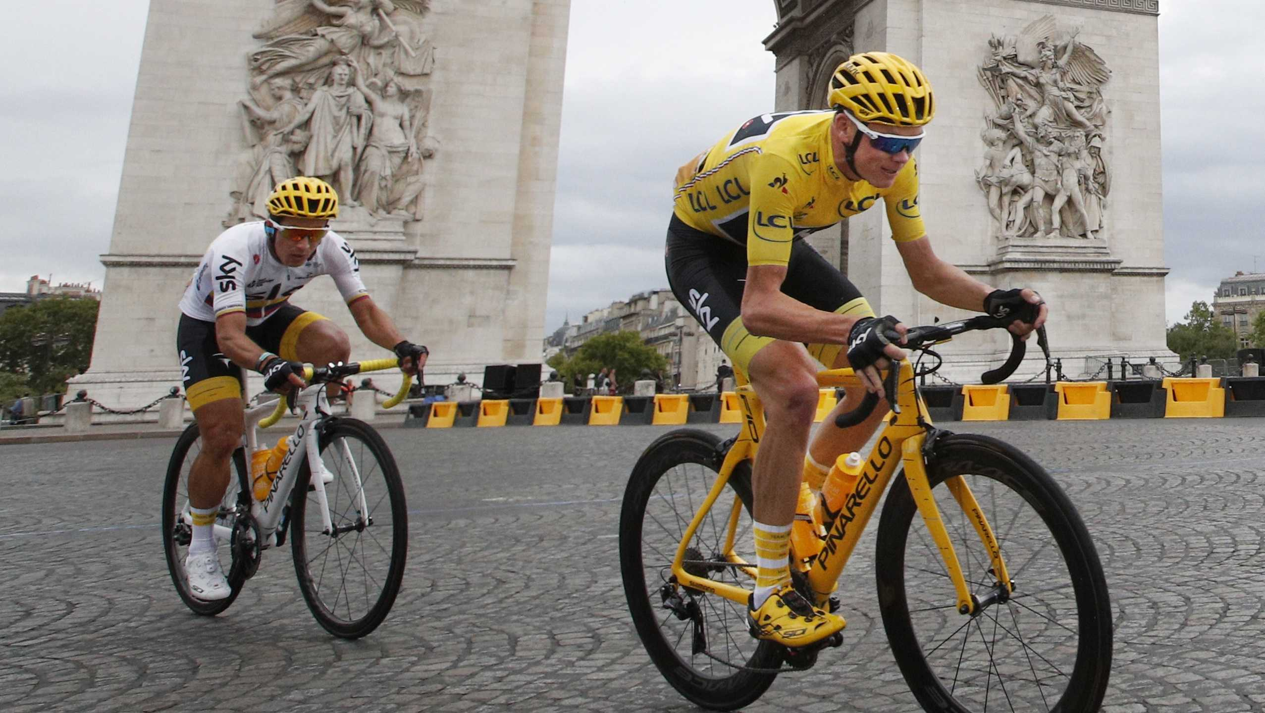 Britain's Chris Froome, wearing the overall leader's yellow jersey, is followed by teammate Colombia's Sergio Henao Montoya, as they pass the Arc de Triomphe during the twenty-first and last stage of the Tour de France cycling race over 64 miles, starting in Montgeron and finish in Paris, France, Sunday, July 23, 2017.