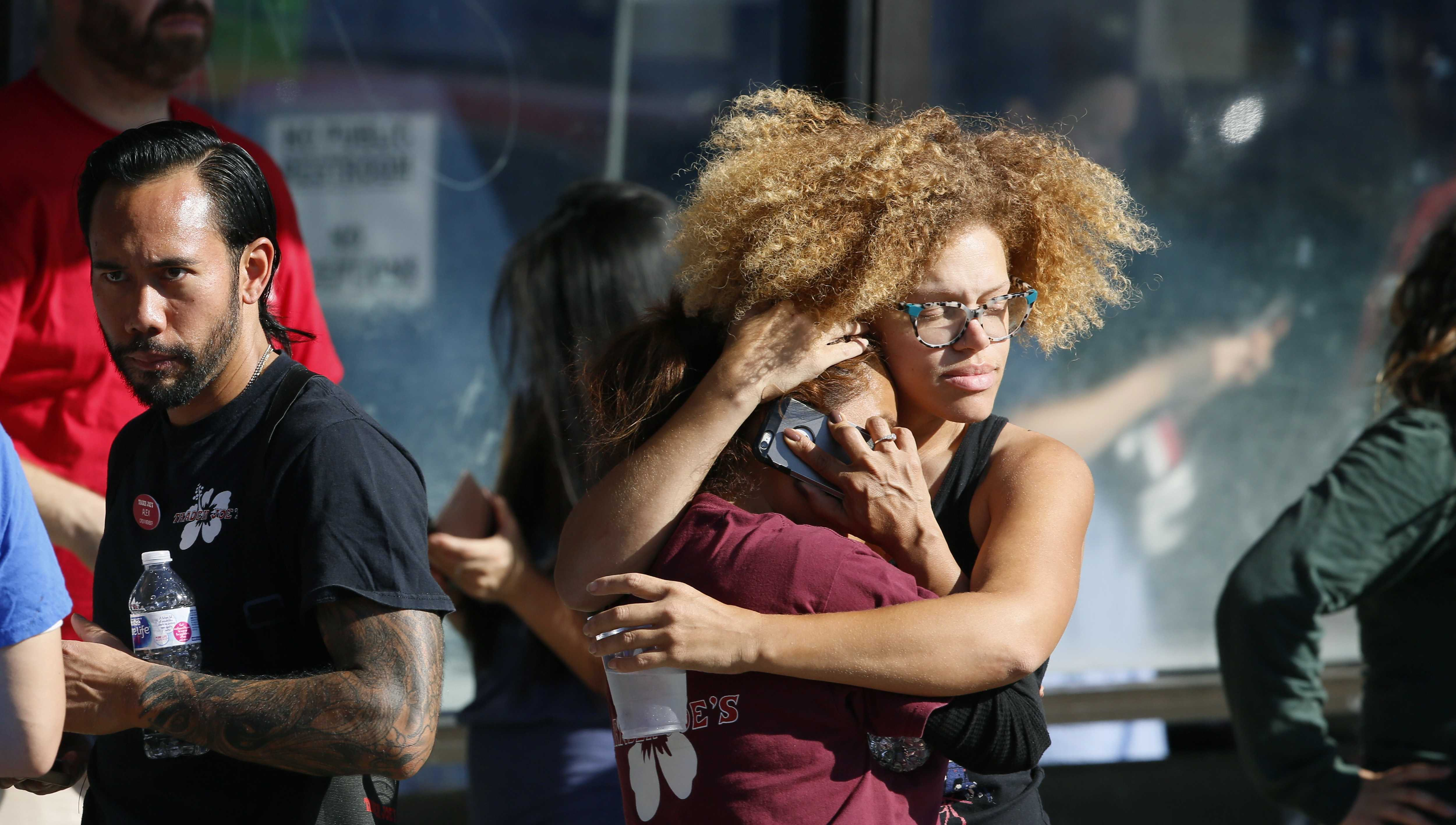 Unidentified Trader Joe's supermarket employees hug after being evacuated by Los Angeles Police after a gunman barricaded himself inside the store in Los Angeles Saturday, July 21, 2018.