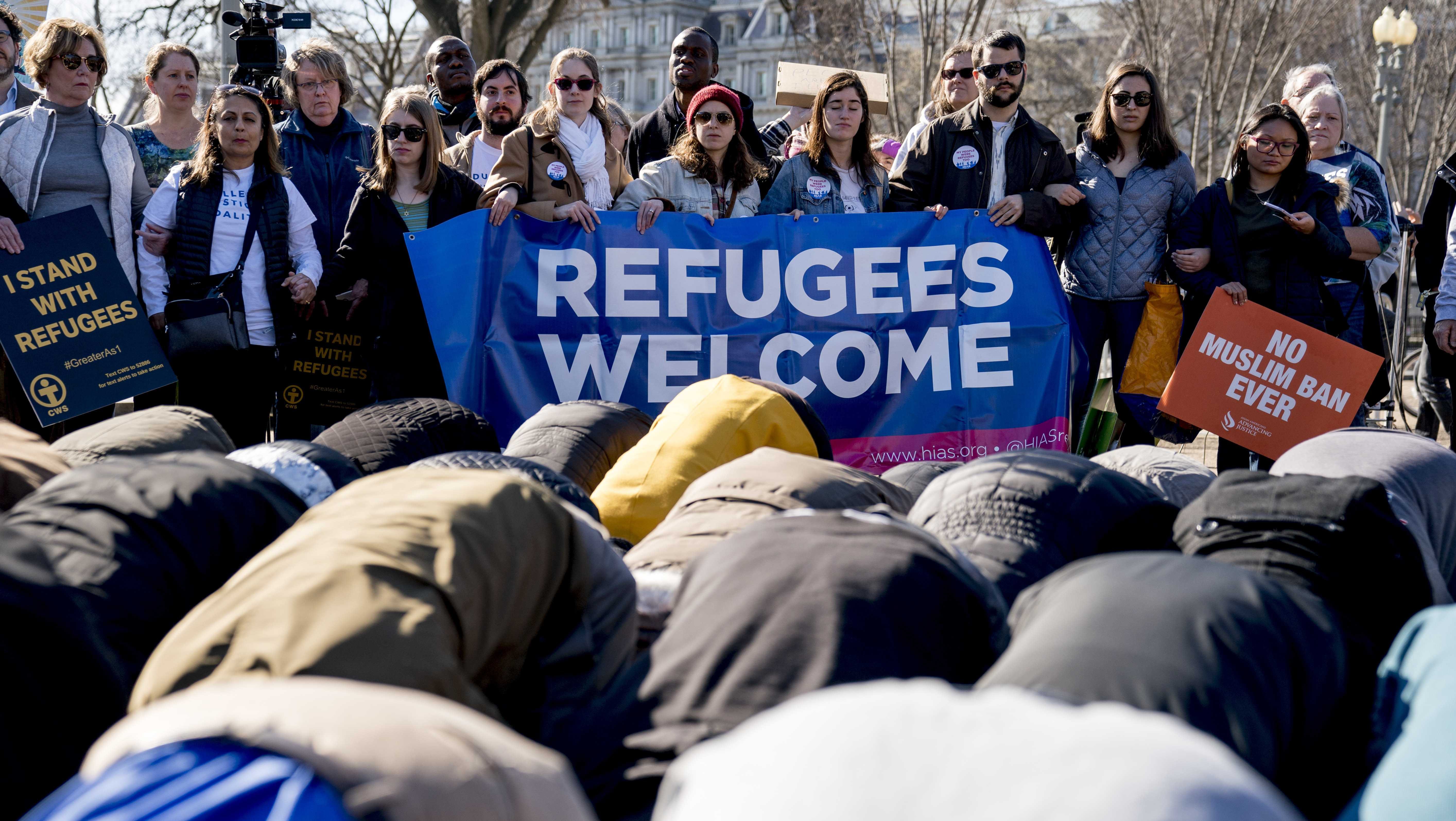 Supporters surround a group who perform the Islamic midday prayer outside the White House in Washington, Saturday, Jan. 27, 2018, during a rally on the one-year anniversary of the Trump Administration's first partial travel ban on citizens from seven Muslim majority countries.