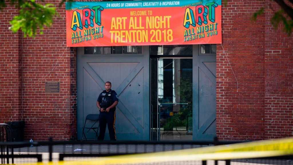 A police officer stands in front as other officers inspect the crime scene at the Roebling Market on June 17, 2018, the morning after a shooting at an all-night art festival injured 22 people and left one suspect dead in Trenton, New Jersey.