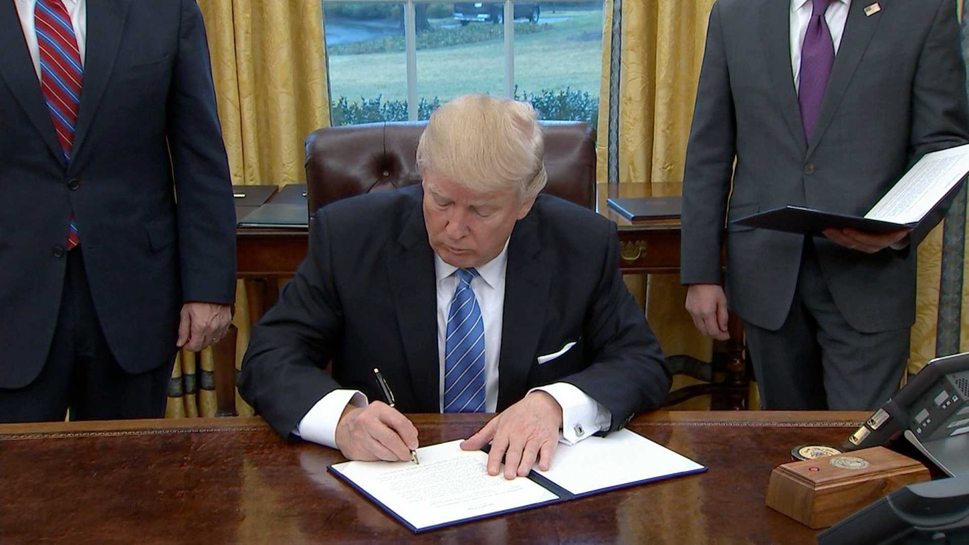 President Donald Trump signs a memorandum to pull the US from the Trans-Pacific Partnership trade deal on Monday, Jan. 23, 2017.