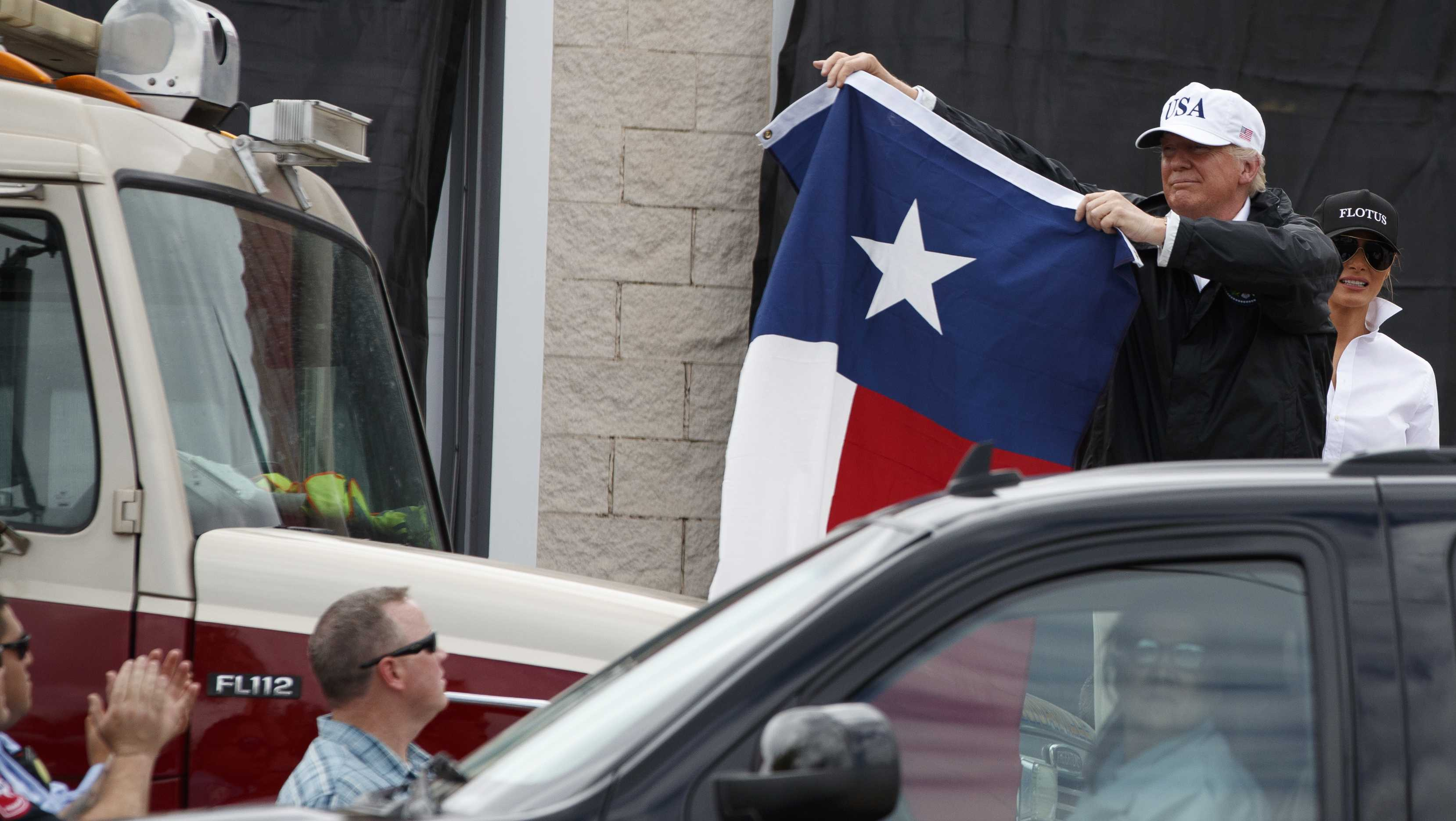 President Donald Trump, accompanied by first lady Melania Trump, holds up a Texas flag after speaking with supporters outside Firehouse 5 Corpus Christi, Texas, Tuesday, Aug. 29, 2017, following a briefing on Harvey relief efforts.