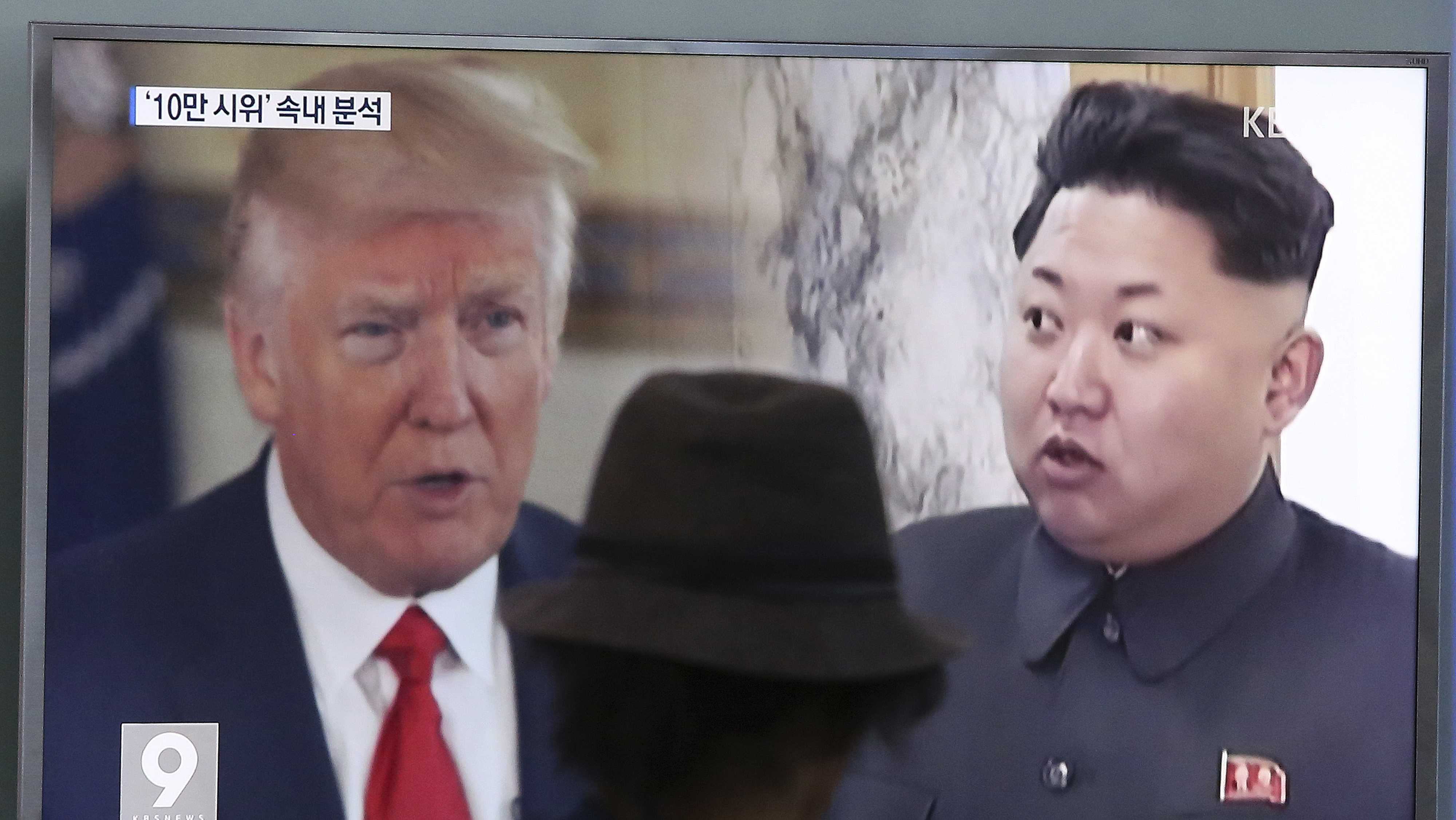 A man watches a television screen showing U.S. President Donald Trump, left, and North Korean leader Kim Jong Un during a news program at the Seoul Train Station in Seoul, South Korea, Thursday, Aug. 10, 2017.