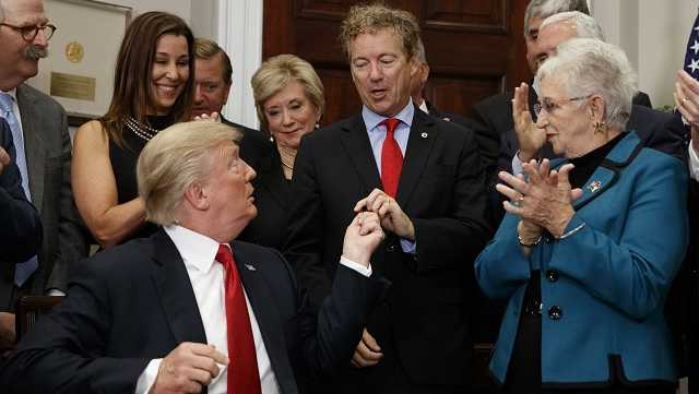 President Donald Trump hands a pen that he used to sign an executive order on health care to Sen. Rand Paul, R-Ky., in the Roosevelt Room of the White House, Thursday, Oct. 12, 2017, in Washington.
