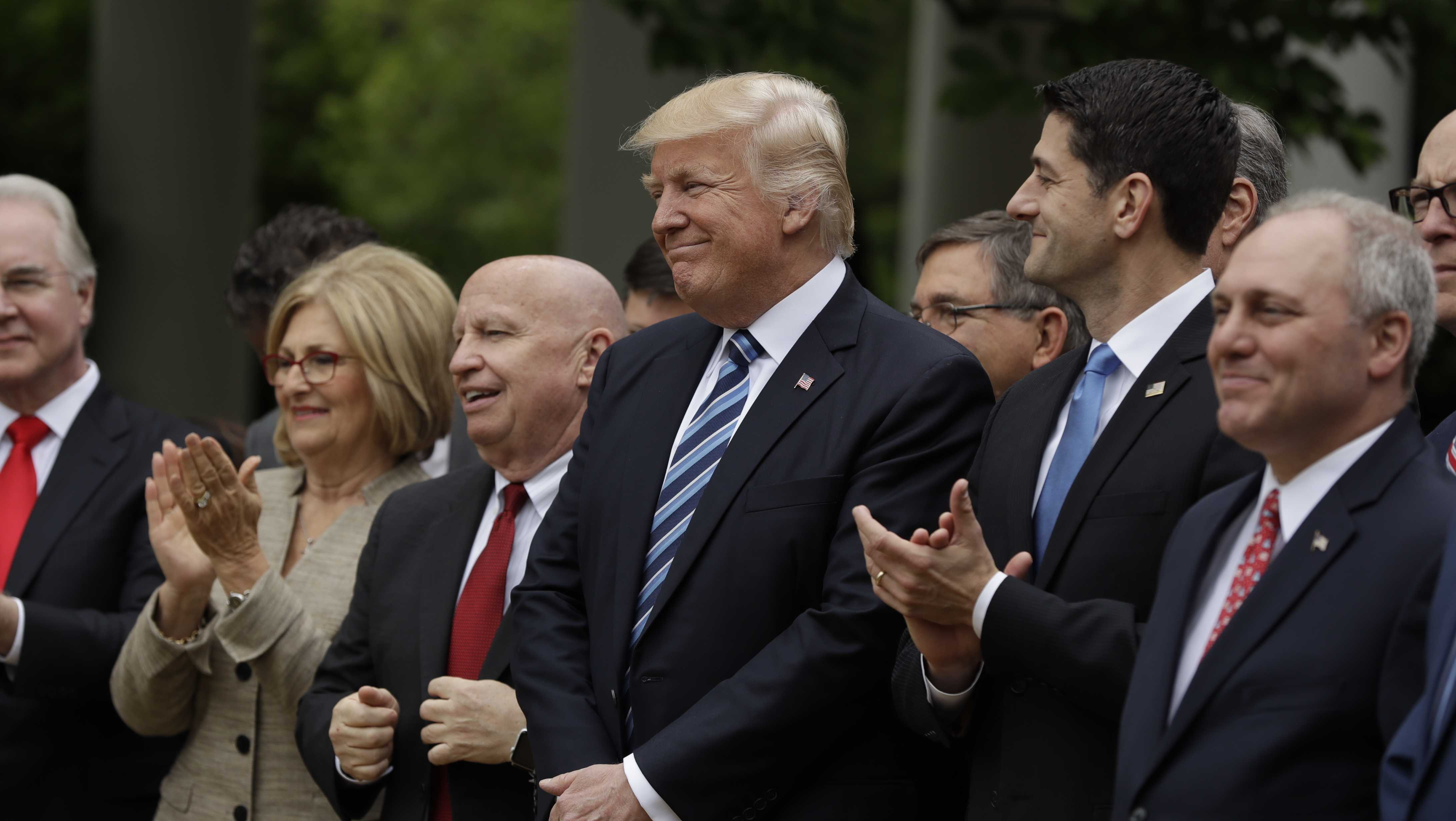 President Donald Trump, flanked by House Ways and Means Committee Chairman Rep. Kevin Brady, R-Texas, and House Speaker Paul Ryan of Wis., are seen in the Rose Garden of the White House in Washington, Thursday, May 4, 2017, after the House pushed through a health care bill.