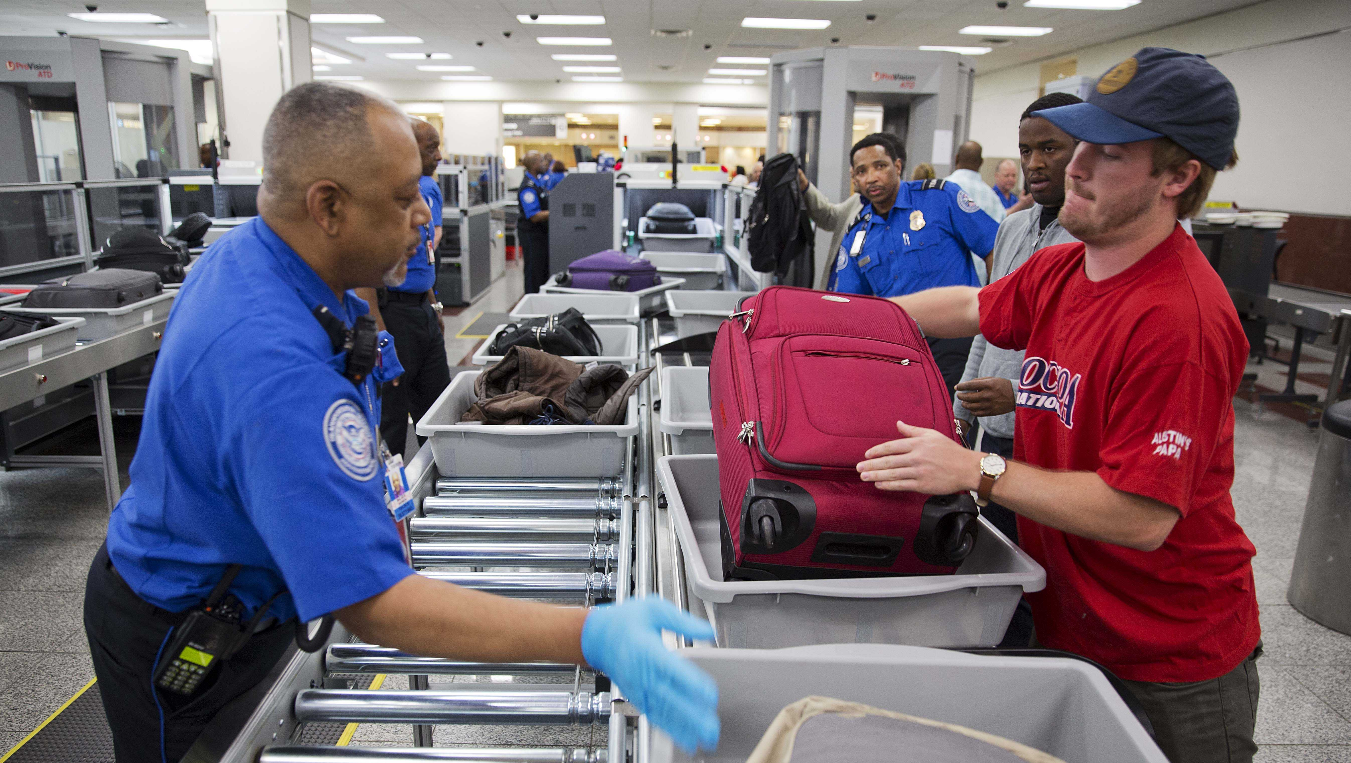 A TSA official helps passengers load their carry-on belongings onto an automated conveyer belt at Hartsfield-Jackson Atlanta International Airport Wednesday, May 25, 2016, in Atlanta.