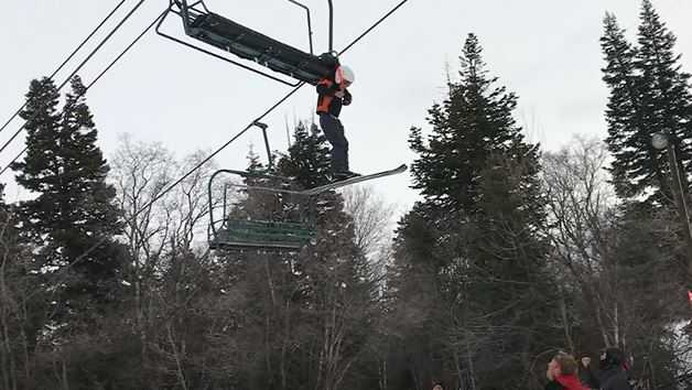 A young boy dangles from a Utah ski lift.