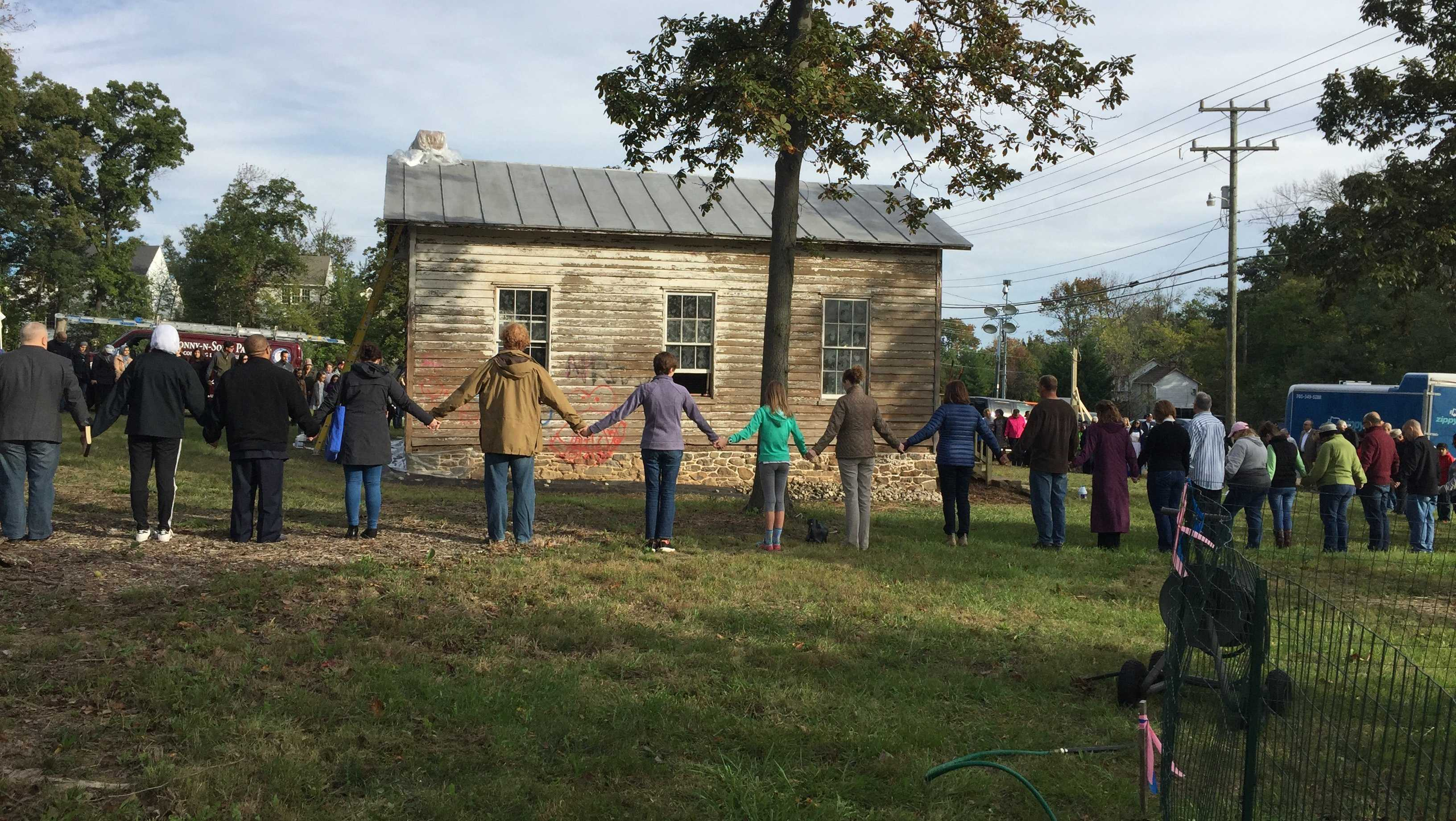 Community members form a unity circle around the school, where they gathered in early October to repair damage done by vandals.