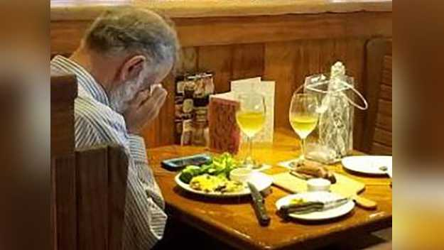 A man holds his face as he has a Valentine's Day meal with his wife's ashes on Feb. 14, 2018.