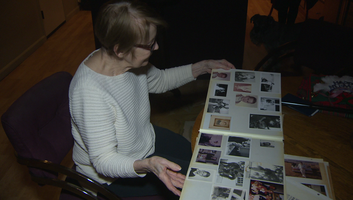 Jeanette Meeker looks through a scrapbook of family photos that include pictures of Mary Tyler Moore.