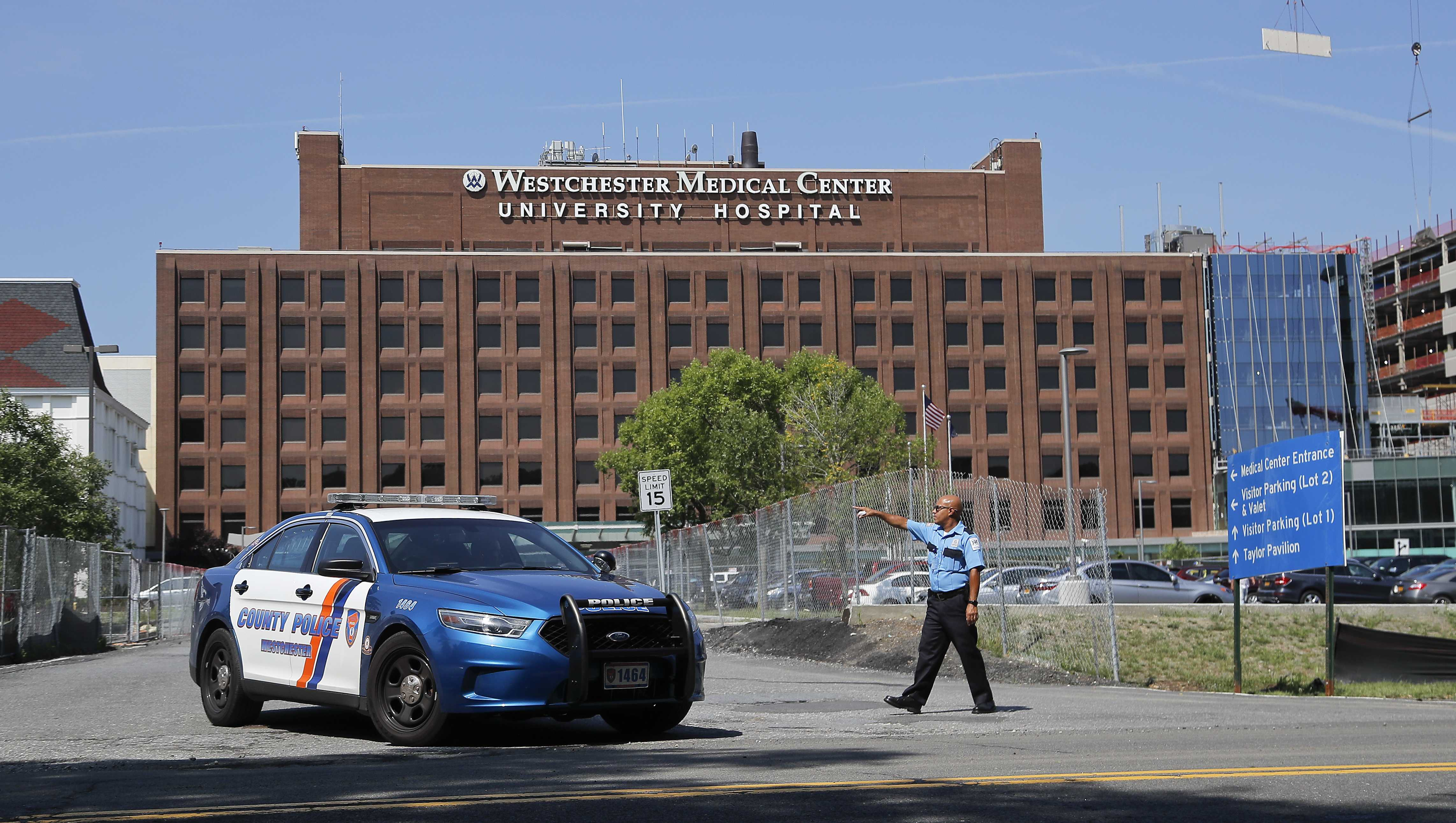 A Westchester Medical Center security guard directs traffic as a Westchester County police car pulls out of the drive to the main entrance of the hospital, Wednesday, Aug. 8, 2018, in Valhalla, N.Y. A man shot a female patient and then killed himself at the suburban New York hospital Wednesday, police said.