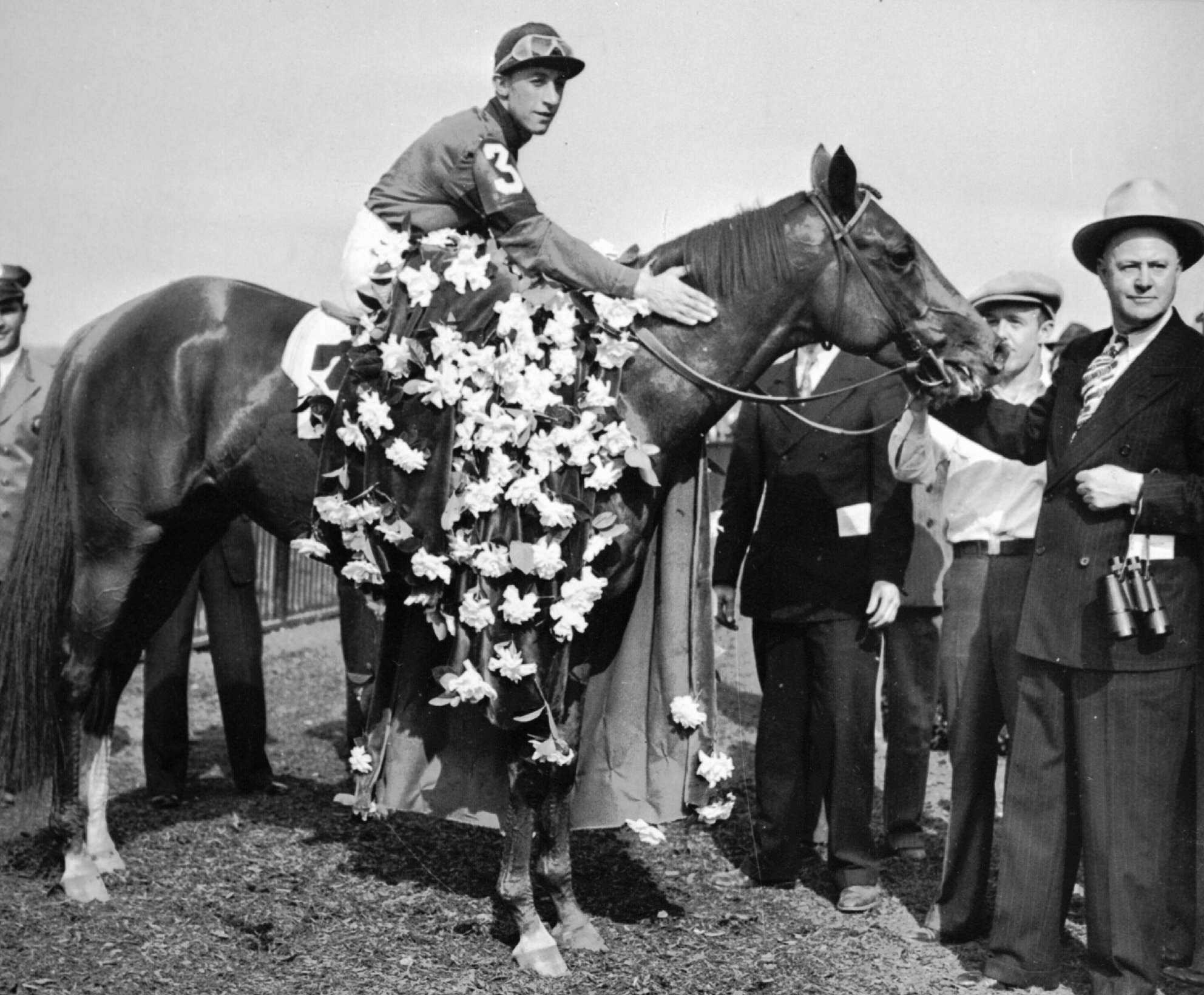 Whirlaway is draped with the floral tribute in the winner's circle at Belmont Park, N.Y., on June 7, 1941 after winning the Belmont Stakes race of the Triple Crown with jockey Eddie Arcaro. Trainer Ben Jones holds the bridle.