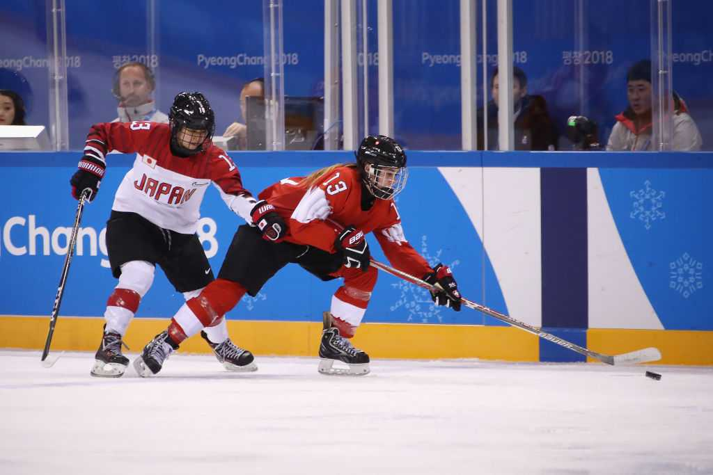 Sara Benz #13 of Switzerland and Moeko Fujimoto #13 of Japan battle for the puck in the first period during the Women's Ice Hockey Preliminary Round- Group B game on day three of the Pyeong Chang 2018 Winter Olympic Games at Kwandong Hockey Centre