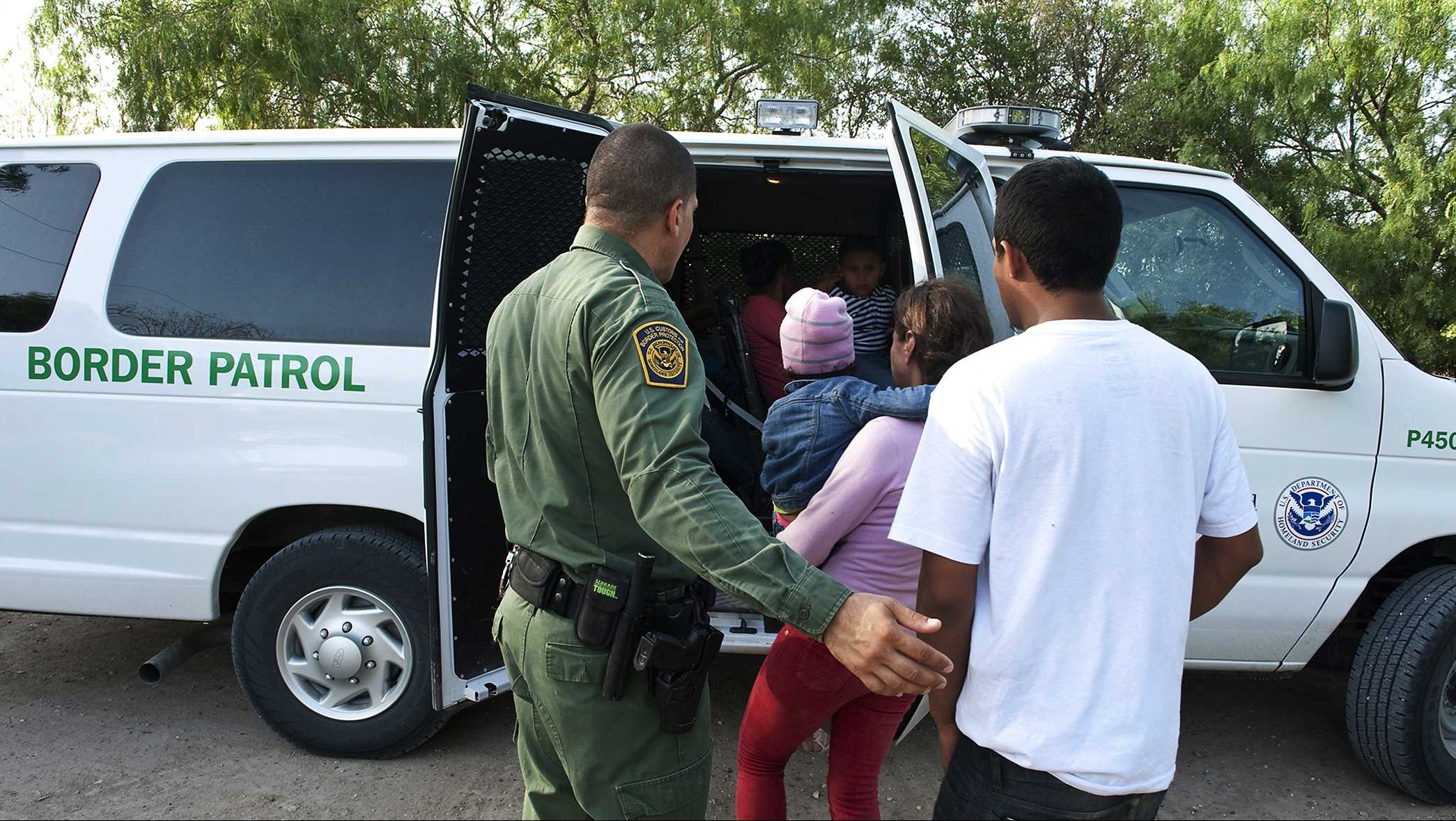 U.S. Customs and Border Protection officers provide assistance to unaccompanied children after they crossed the border into the United States illegally.  (June 2014)