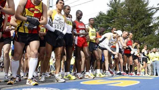 Elite men runners prepare to cross the start line of the Boston Marathon in Hopkinton, Mass.